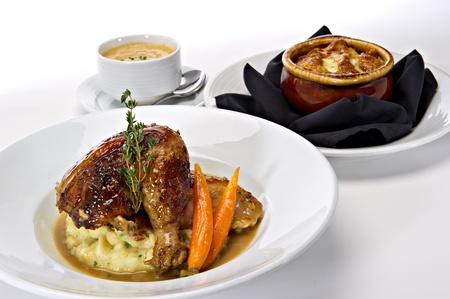 pollo rostizado: Pierna asador de pollos asados ??servidos sobre puré de papas con zanahorias y salsa gravy. Una ramita de romero fresco, verde tops esto. Tazones de sopa caliente se presentan en el fondo. Foto de archivo