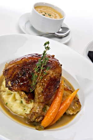 pollo rostizado: Pierna asador de pollos asados ??servidos sobre pur� de papas con zanahorias y salsa gravy. Una ramita de romero fresco, verde tops esto. Un plato caliente de sopa aparece en el fondo.