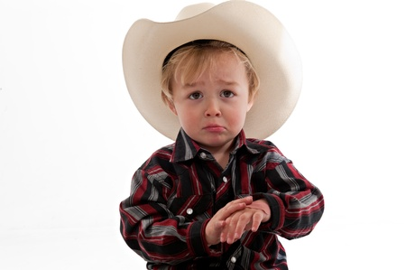 Portrait of a sad little boy in a cowboy hat. He is frowning and holding one hand in his other. photo