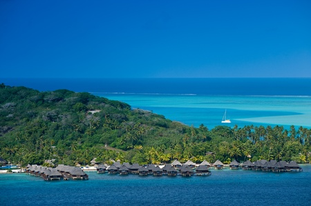 polynesia: View over beautiful turquoise lagoon of bungalows, island and boats. Bora Bora Island, Tahiti, Society Islands, French Polynesia. Stock Photo