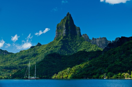 polynesia: View from the water of the tropical bay on Moorea with a sailboat anchored.  Moorea Island Roto Nui Volcanic Mountain pushes towards the sky. Stock Photo