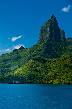 tahiti: View from the water of the tropical bay on Moorea with a sailboat anchored.  Moorea Island Roto Nui Volcanic Mountain pushes towards the sky. Stock Photo