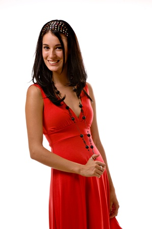 A young pretty brunette wearing a red summer dress is holding her long necklace playfully and smiling at the camera. Stock Photo
