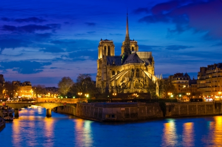 paris at night: Stunning Notre-Dame Cathedral (1163) and Parisian apartments along the banks of the river Seine, Paris, France illuminated at night.