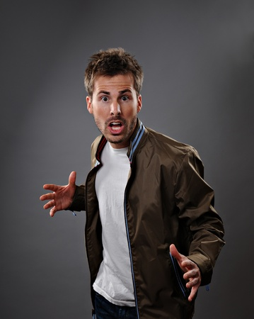 Portrait from the waist up of a caucasian man who is surprised and scared.  Studio shot on a gray background. Stock Photo - 10828666