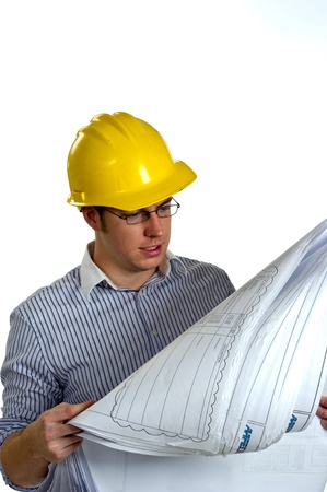 Young Businessman wearing a hard hat is reviewing construction blue prints.