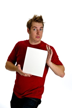 engaging: Engaging young man in a red shirt and jeans, with wild hair, holding a blank white sign in front of his chest. Stock Photo