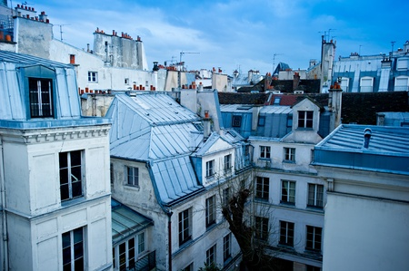 urban apartment: View of a Paris neighborhood skyline, featuring mostly rooftops from the top floor of an apartment building in Paris, France.