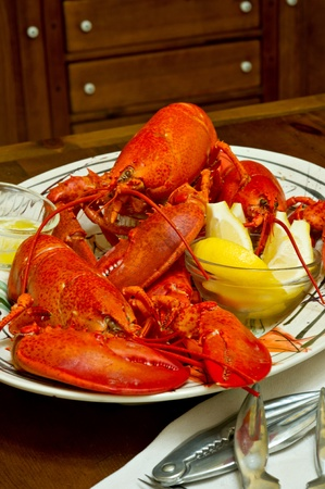 lobster: Boiled Maine lobsters served with melted butter and lemon slices.  There are 3 whole lobsters on the platter.