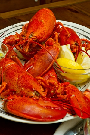 Boiled Maine lobsters served with melted butter and lemon slices.  There are 3 whole lobsters on the platter.