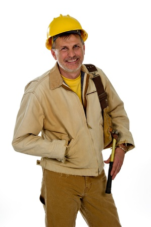 A professional male construction contractor worker is wearing a hard hat and holding a tool belt. Фото со стока
