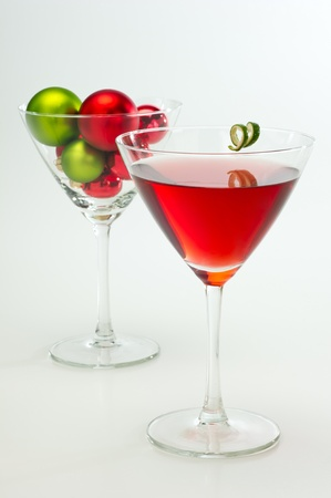 Red cranberry martini with festive Christmas ornaments in the background. photo