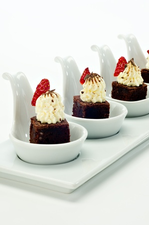 Beautiful square bite size brownies for four topped with whipped cream, dark chocolate shavings and a strawberry and served on white porcelain tasting spoons. Stock Photo - 10905242