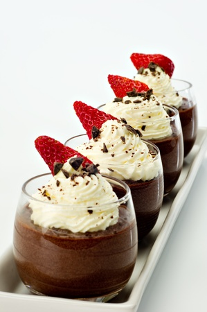 mousse: Chocolate Mousse for four topped with whipped cream, dark chocolate shavings and a strawberry.