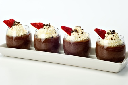 Chocolate Mousse for four topped with whipped cream, dark chocolate shavings and a strawberry.