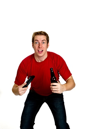 Excited sports fan in a red shirt and jeans, holding a beer in one hand and a TV remote control in the other, watching the big game.  Studio shot isolated on white.