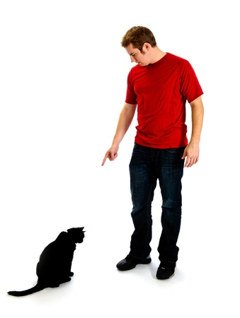 Young man in a red shirt and jeans, is pointing down at a black cat who has his head down knowing he was misbehaving.  Studio shot isolated on white.