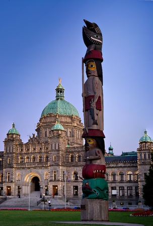 View of a totem pole in front of the parliament building at night located in Victoria, British Columbia, Canada.