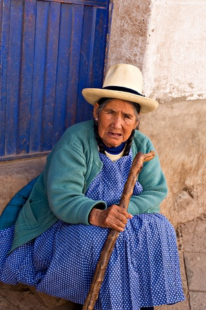 peruvian ethnicity: Pisac, Peru - August 17, 2008: Quechua woman rests on a step at a market in Pisac, Peru. Pisac Market in the Sacred Valley is a popular destination for tourism from all around the world.