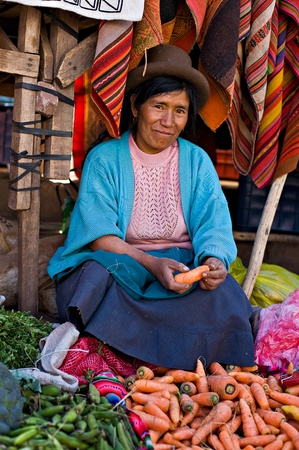 Pisac, Peru - August 17, 2008: Quechua woman sells vegetables at a market in Pisac, Peru. Pisac Market in the Sacred Valley is a popular destination for tourism from all around the world.