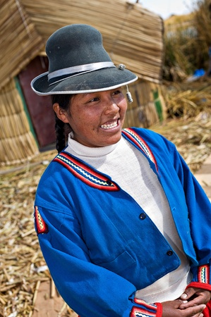 peruvian ethnicity: Lake Titicaca, Peru - August 22, 2008: Quechua girl smiles on Uros, a floating reed island, on Lake Titicaca, Peru.  Lake Titicaca is a popular destination for tourism from all around the world.