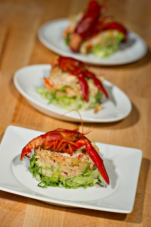 Fresh prepared Crayfish beautifully plated over a round of green lettuce topped with a seafood salad. photo