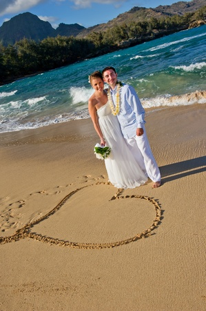 Just Married. Beautiful young couple on the beach on their wedding day.  They are standing next to a heart drawn in beach sand. photo