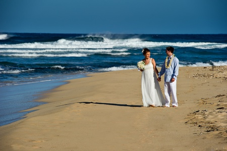 Just Married. Beautiful young couple on the beach on their wedding day.  They are walking and gazing lovingly into each others eyes.