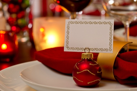 Elegant Christmas place setting place with ornament card holder on a white plate.