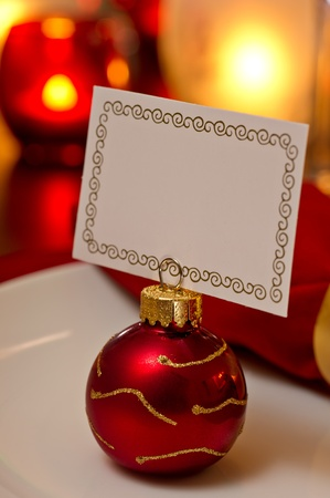 place card: Elegant Christmas place setting place with ornament card holder on a white plate.