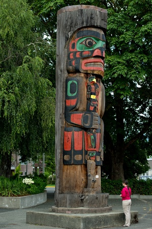 A woman is looking at a beautiful totem pole located in Duncan, British Columbia.
