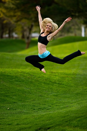 Beautiful blond young woman practicing yoga in the park on a green lawn with trees in the distance.  She is jumping in the air with her arms overhead. photo