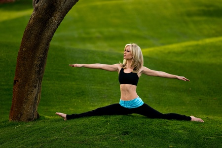 Beautiful blond young woman doing the splits with arms out in the park on a green lawn.