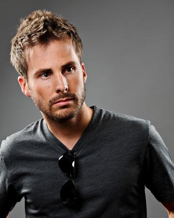 pelo castaño claro: Joven bella modelo masculino que llevaba un camiseta gris. Tiene una expresión seria y se disparó sobre un fondo gris.