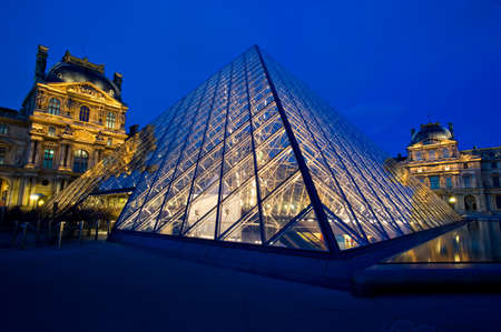 PARIS - March 26: Louvre Pyramid shines at dusk on March 26, 2010 in Paris. Louvre is the biggest Museum in Paris displaying over 60,000 square meters of exhibition space.