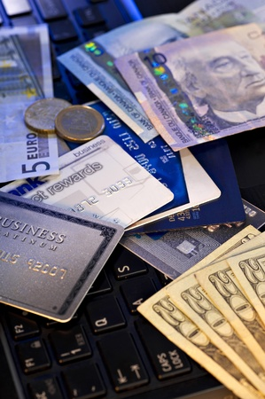 US and Canadian Dollars, Euros and credit cards stacked on top of a laptop computer.  Studio shot.