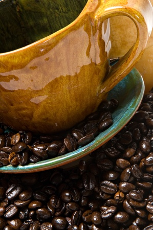 Close up of a coffee mug and saucer overflowing with dark roasted coffee beans.  Shallow depth of field.