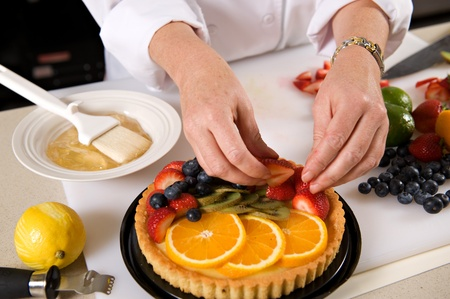 Hands of a pastry chef placing fresh fruit on a custard tart. Stock Photo