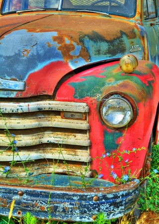 Detail of the front end of an old rusted abandoned vintage truck.  There are wild flowers growing in front of it.
