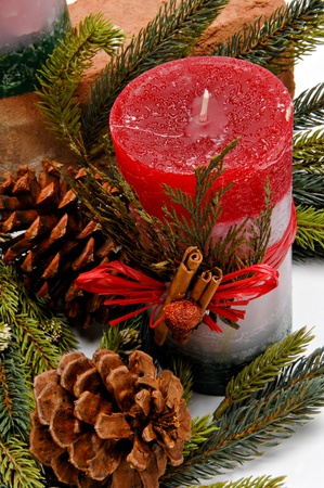 Red, white and green festive candle with green cedar leaves and cinnamon sticks tied on with twine for Christmas. The candle is placed among pine branches and pine cones. Stock Photo - 11419278