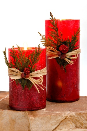 scented candle: Red festive candles with green cedar leaves tied on with twine for Christmas.  The candles are lit and glowing red.
