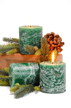 Trio of green festive candles. 2 of the candles are lit and all are placed among pine branches and pine cones.