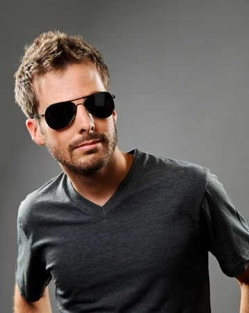 Young beautiful male model wearing a gray t-shirt and dark glasses.  He is exuding confidence. Studio shot on a gray background.