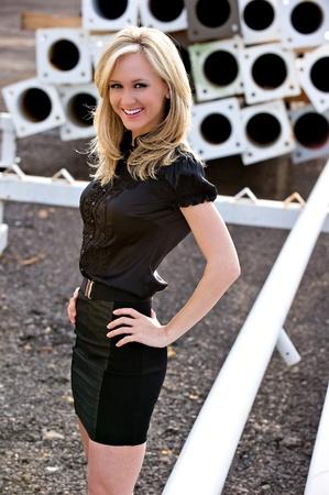 mini jupe: Belle blonde mannequin avec ses mains sur sa hanche, portait une jupe courte noire posant à l'extérieur d'un chantier de construction.