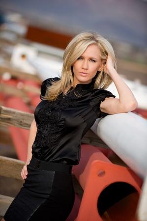 mini jupe: Belle blonde mannequin appuyé contre les matériaux de construction, de porter une jupe courte noire posant à un chantier de construction extérieur. Banque d'images