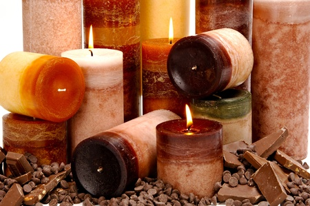 morsels: Assortment of chocolate scented candles arranged among chocolate bars and morsels. Stock Photo