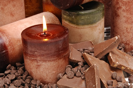 morsels: Assortment of brown chocolate scented candles arranged among chocolate bars and morsels.
