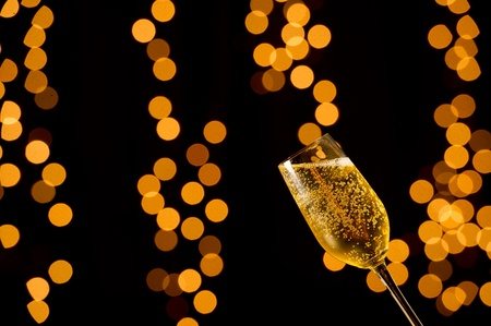 Single glass of Champagne on black background with out of focus yellow and orange lights.  Studio Shot.  photo