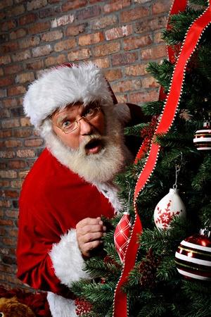 Santa Claus looking surprised as he is sneaking around the Christmas Tree. photo