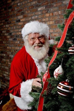 Santa Claus smiling as he is sneaking around the Christmas Tree. photo